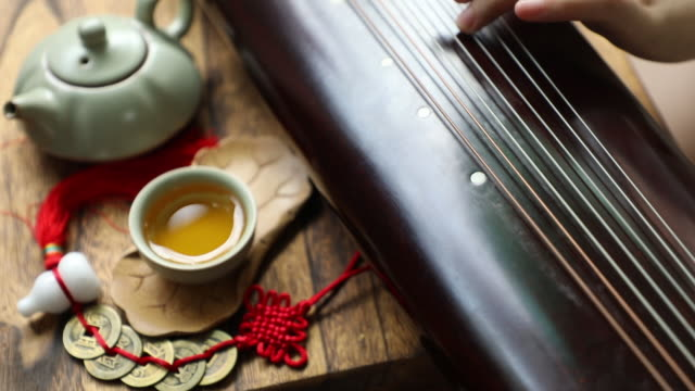 asian woman playing the guqin (an ancient chinese string musical instrument) - musical instrument string stock videos and b-roll footage
