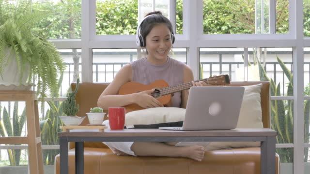 vídeos de stock, filmes e b-roll de mulher asiática tocando música de guitarra ukelele e usando chamada de videoconferência de computador portátil tocando com amigo. teleconferência para tocar música covid-19 quarentena - ukulele