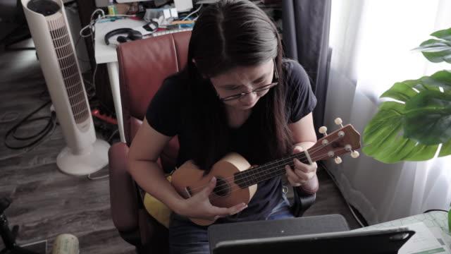 vídeos de stock, filmes e b-roll de mulher asiática jogando ukulele com professor usando laptop teleconferência. - ukulele