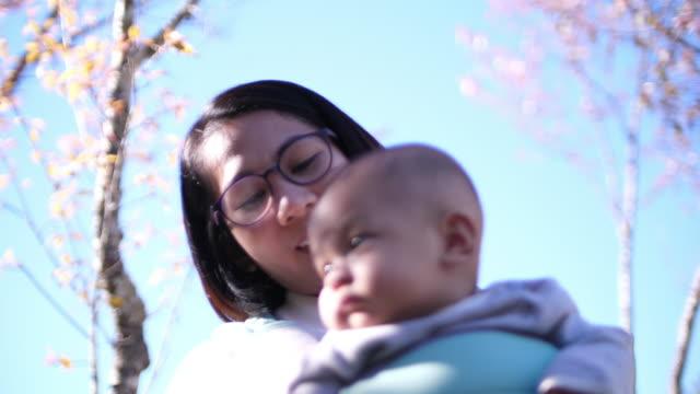 桜の花の下で彼女の赤ちゃんと遊んで SLO MO アジア女性