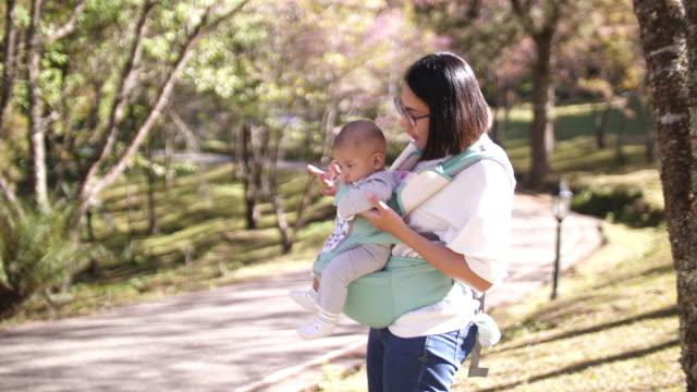 桜の花の下で彼女の赤ちゃんと遊んで slo mo アジア女性 - 生後2ヶ月から5ヶ月点の映像素材/bロール