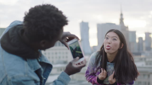 Asian woman posing on roof to photographer with smartphone