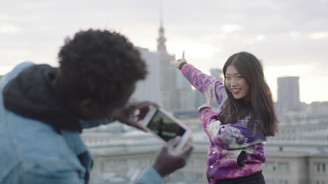 Asiatique femme posant sur le toit au photographe avec smartphone