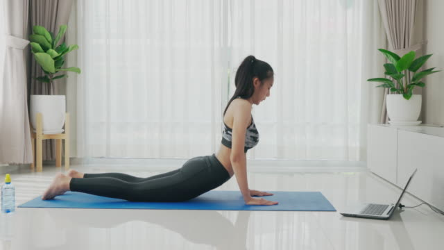 asian woman practice or exercise indoor cobra pose while watching videos fitness workout class live streaming online on laptop in the living room at home. - bodyweight training stock videos & royalty-free footage