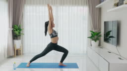 Asian woman practice or exercise indoor Warrior 2 pose while watching videos fitness workout class live streaming online on laptop in the living room at home.
