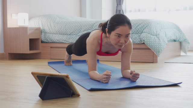 asian woman practicing yoga at home with laptop in bedroom - routine stock videos & royalty-free footage