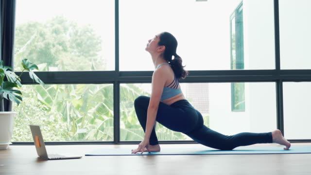 vídeos de stock, filmes e b-roll de mulher asiática praticando yoga em casa com laptop - equilíbrio vida trabalho
