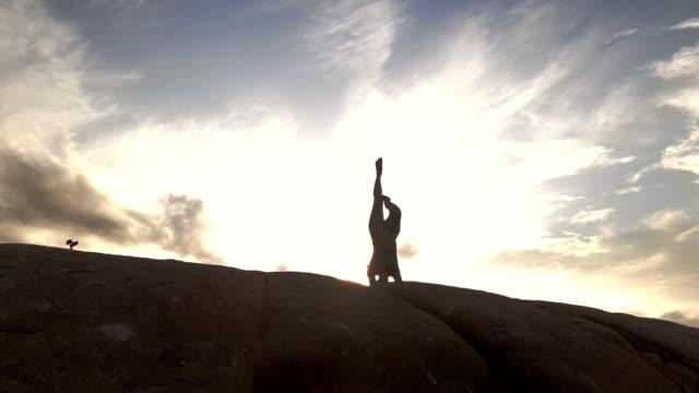 vídeos de stock, filmes e b-roll de mulher asiática praticando yoga na montanha . a pessoa medita ao ar livre e desfruta do nascer do sol laranja. - só uma mulher jovem