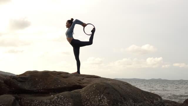vidéos et rushes de femme asiatique pratiquant le yoga à la montagne. - belle femme