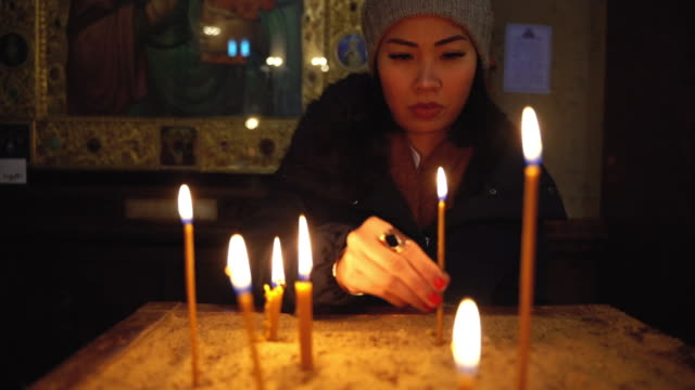 asian woman praying and lighting up a candle in church - christianity stock videos & royalty-free footage