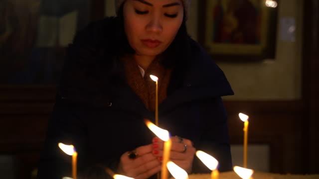 vídeos de stock, filmes e b-roll de mulher asiática rezando e acendendo uma vela na igreja - candlelight