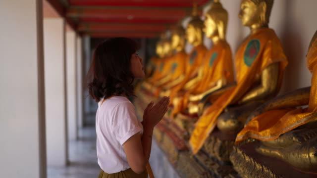 亞洲婦女祈禱與佛陀在寺廟 - 寺院 個影片檔及 b 捲影像