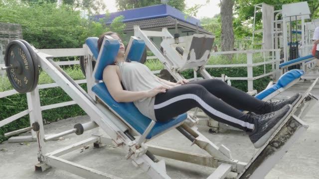 vídeos de stock, filmes e b-roll de mulher asiática empurrando equipamentos de peso por perna - músculo humano