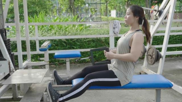 vídeos de stock, filmes e b-roll de mulher asiática empurrando equipamento de peso, câmera lenta - músculo humano