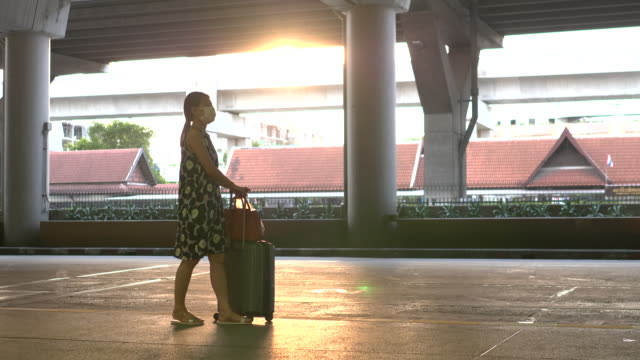 asian woman put on protective mask outside airport terminal with trolley luggage cart - luggage trolley stock videos & royalty-free footage