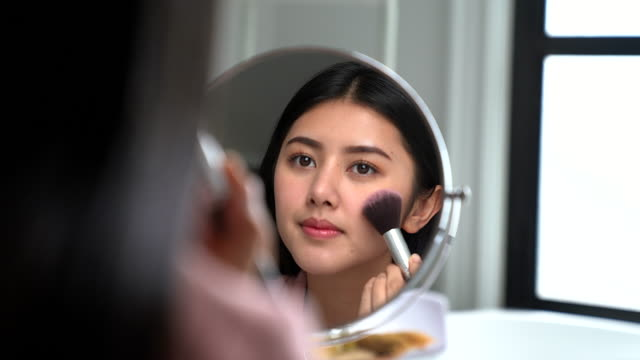 asian woman putting on her makeup in front of the bathroom mirror - mascara stock videos & royalty-free footage