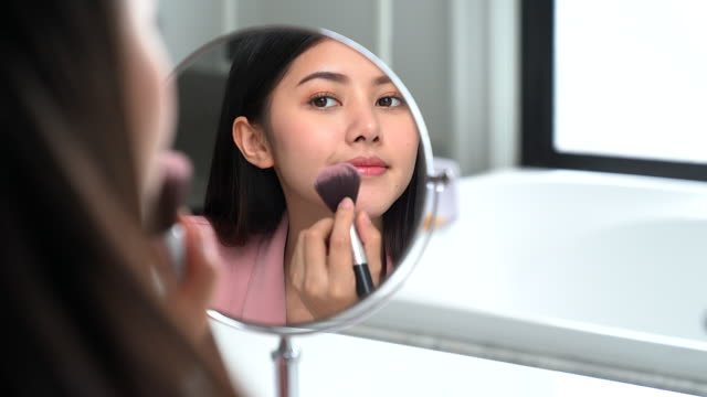 asian woman putting on her makeup in front of the bathroom mirror - highlights hair stock videos & royalty-free footage