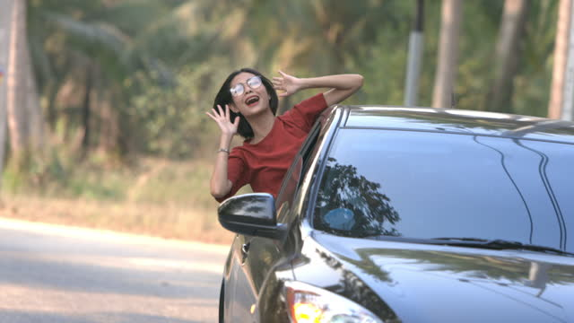 asian woman raise and motion her hand outside the car during her friend driving the car - human limb stock videos & royalty-free footage