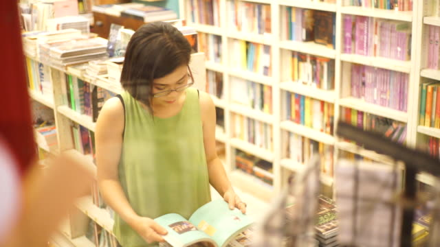 asian woman reading a book at the bookstore against shelves backgrounds. - book shop stock videos & royalty-free footage