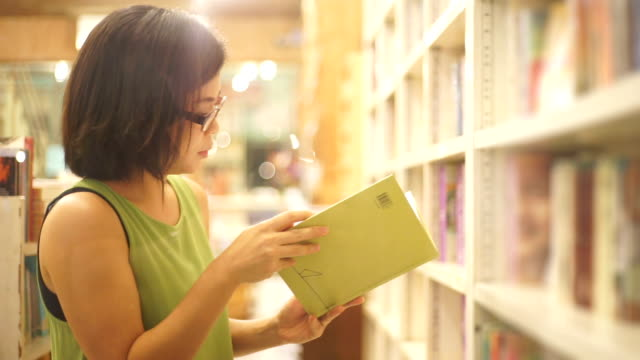 asian woman reading a book at the bookstore against shelves backgrounds. - bookstore stock videos & royalty-free footage