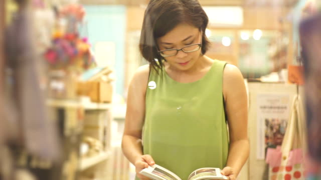 asian woman reading a book at the bookstore against shelves backgrounds. - souvenir stock videos and b-roll footage