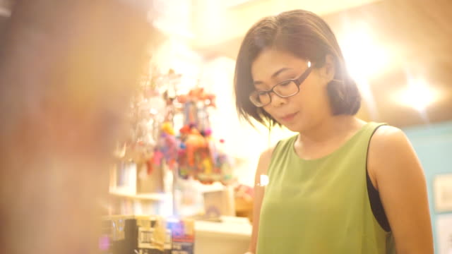 asian woman reading a book at the bookstore against shelves backgrounds. - bookseller stock videos and b-roll footage