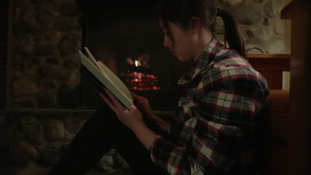 asian woman reading a book by fireplace - chinaface stock videos & royalty-free footage