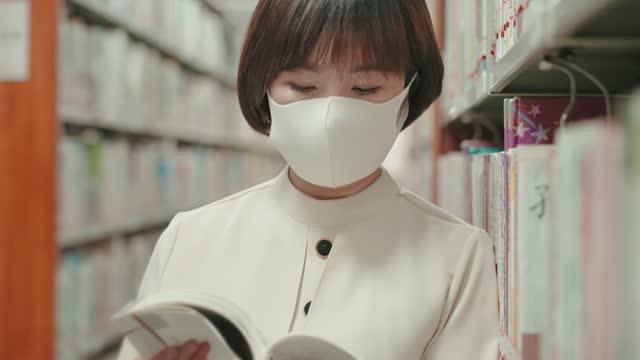 vidéos et rushes de femme asiatique lisant un livre sur étagère dans la bibliothèque - littérature