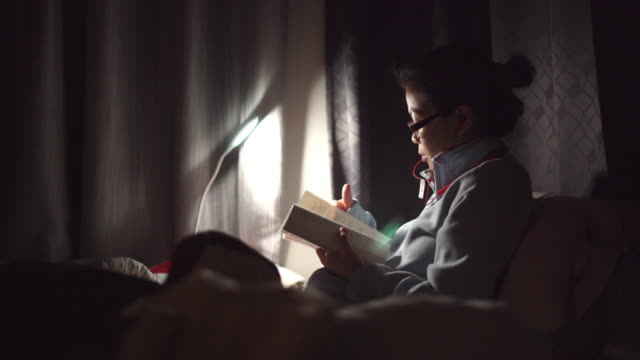 donna asiatica che legge un libro sul letto di notte - electric lamp video stock e b–roll