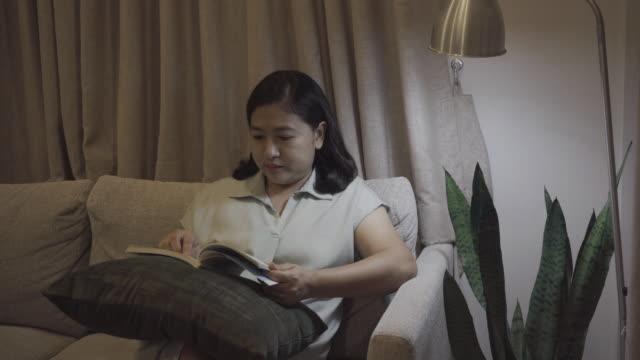 vidéos et rushes de femme asiatique affichant un livre - seulement des jeunes femmes