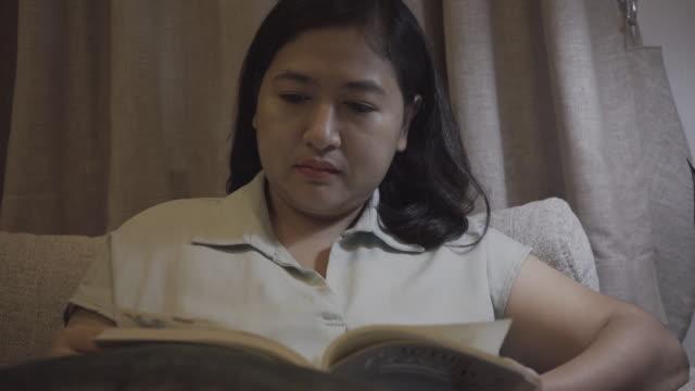 vídeos de stock e filmes b-roll de asian woman reading a book - só mulheres jovens