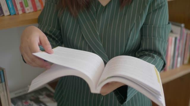 アジアの女性は公共図書館で本を読みます。 - 公共図書館点の映像素材/bロール