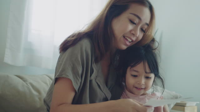 vídeos de stock e filmes b-roll de asian woman reading postcard on mothers day and smiling with her daughter - mensagem