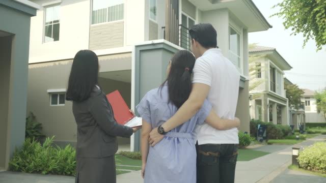 アジアの女性不動産ブローカーエージェントは、それを購入するために探して、関心を探して若いアジアのカップルの恋人に彼女のファイルに家の詳細を示しています。新しい家を買う。 - 助言点の映像素材/bロール