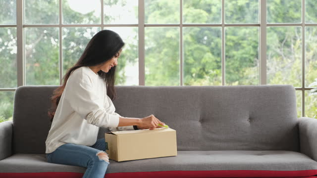 vídeos de stock e filmes b-roll de asian woman received cardboard box for online shopping store and delivery to home. woman opening postal package sitting on sofa in living room - viciado em compras