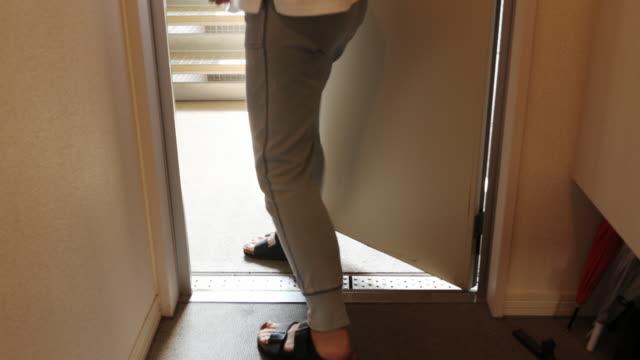 アジアの女性は、小さなアパートの入り口の前に到着した荷物を受け取ります - 建物入口点の映像素材/bロール
