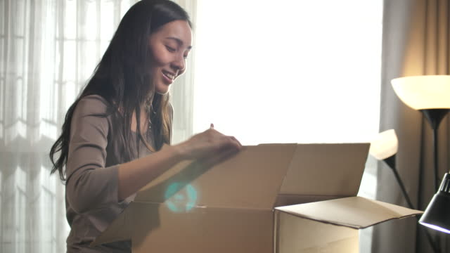 asian woman receiving a parcel and opening box very happy at home - letterbox stock videos & royalty-free footage