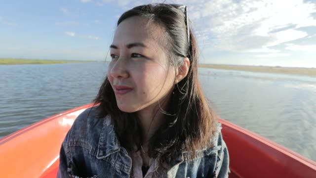 vídeos y material grabado en eventos de stock de mujer asiática relajante y mirando a ver el lago en el barco de tour por la mañana, lenta, solo de mujer concepto trave - sólo mujeres jóvenes