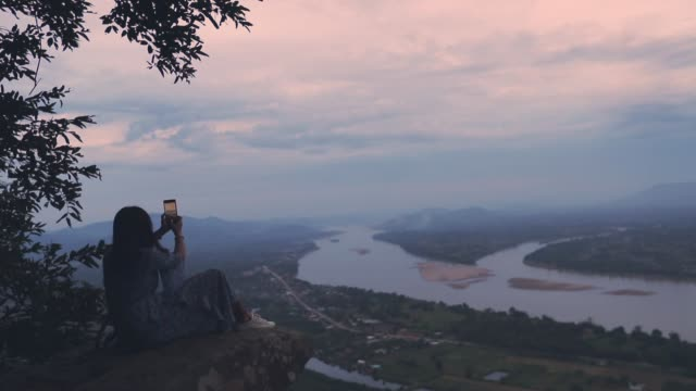 asian woman relaxing and taking a photo of mountain view at twilight by smartphone ,slow motion, concept woman solo travel - mekong delta stock videos & royalty-free footage