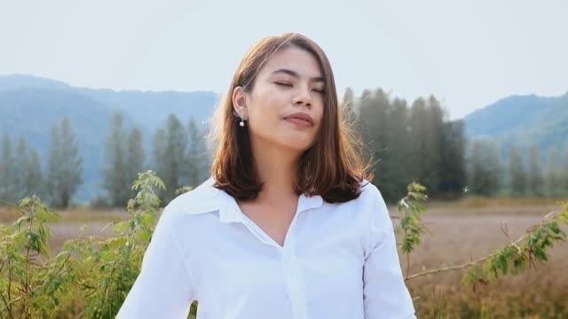 vídeos y material grabado en eventos de stock de mujer asiática relajante en la naturaleza al aire libre, concepto de estilo de vida. - camisa con botones