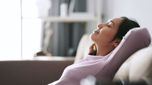asian woman relaxing at sofa - tranquility stock videos & royalty-free footage