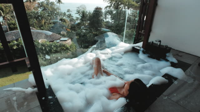 asian woman relaxing in outdoor bath with tropical sea luxury spa hotel, lifestyle concept - coastal feature stock videos & royalty-free footage