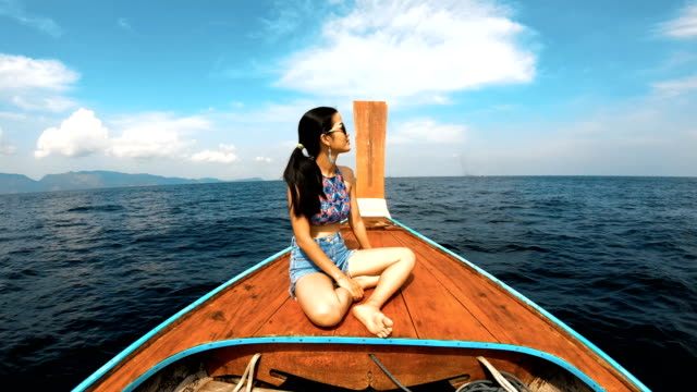 asian woman relaxing in thai taxi boat at lipe, satun, thailand - water taxi stock videos & royalty-free footage