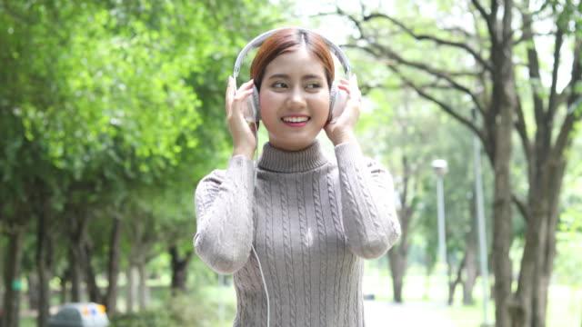 アジア女性は公園で音楽を聴いてリラックス - indian ethnicity点の映像素材/bロール
