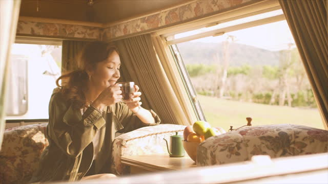 asian woman relaxing, sitting, drinking coffee in a van camping vecation solo - bag stock videos & royalty-free footage