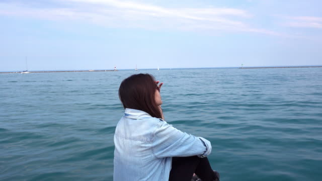 Asian Woman relaxing with Lake Michigan background, Chicago, Illinois, USA