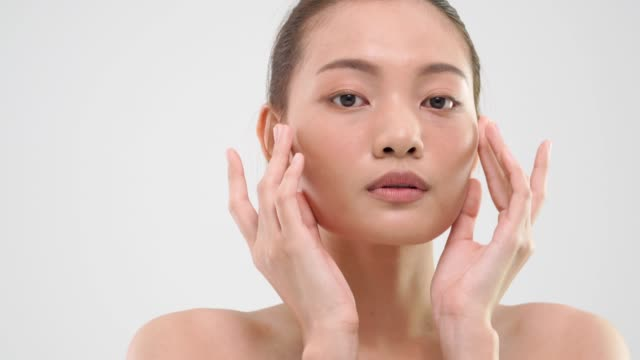 asian woman rubbing skin with beauty skin care product on white background. - skin feature stock videos & royalty-free footage