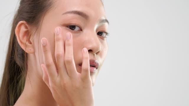 vidéos et rushes de femme asiatique se frottant la peau avec le produit de soin de peau beauté sur fond blanc. - seulement des jeunes femmes