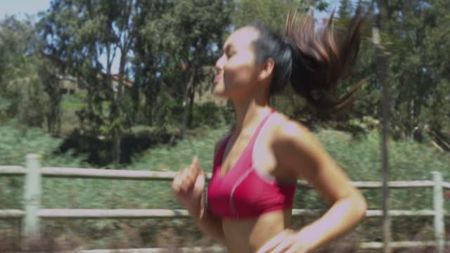 asian woman running at the park - joggerin stock-videos und b-roll-filmmaterial