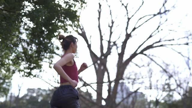 公園で走っているアジア人女性 - スポーツ用語点の映像素材/bロール